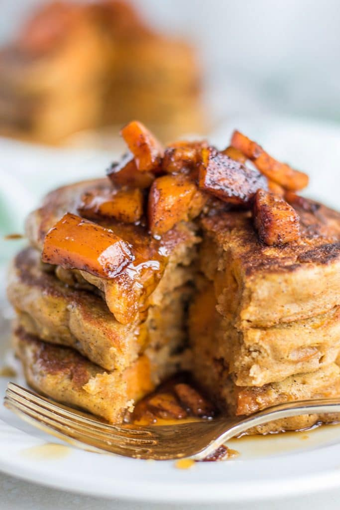A stack of butternut squash pancakes with a bite taken out of them.