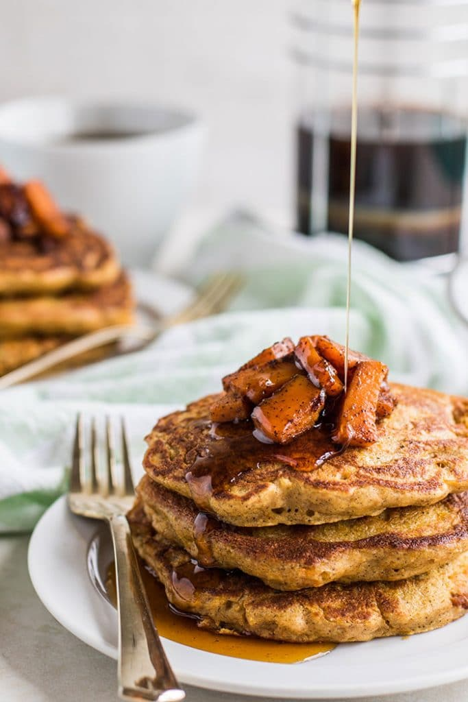 Gluten free pancakes with caramelized butternut squash, being drizzled with syrup.