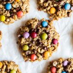 A close up of colorful gluten free monster cookies studded with chocolate and candy coated chocolate drops.