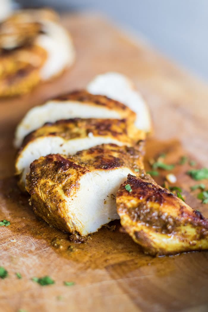 A cutting board with sliced moroccan spiced chicken breasts.