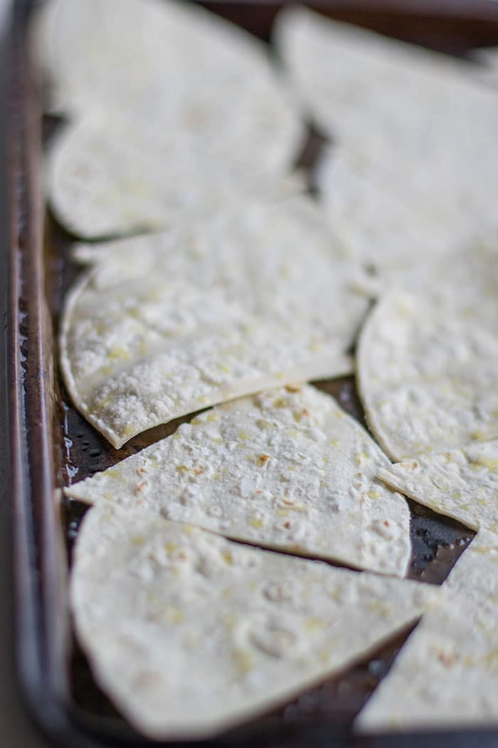 A baking tray with cut tortillas on it ready to sprinkle with sea salt and bake.