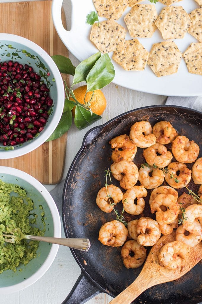 Mini Shrimp Tostadas with Pomegranate Guacamole / The perfect healthy party appetizer! Blackened shrimp, guacamole, and a tangy pomegranate salsa.