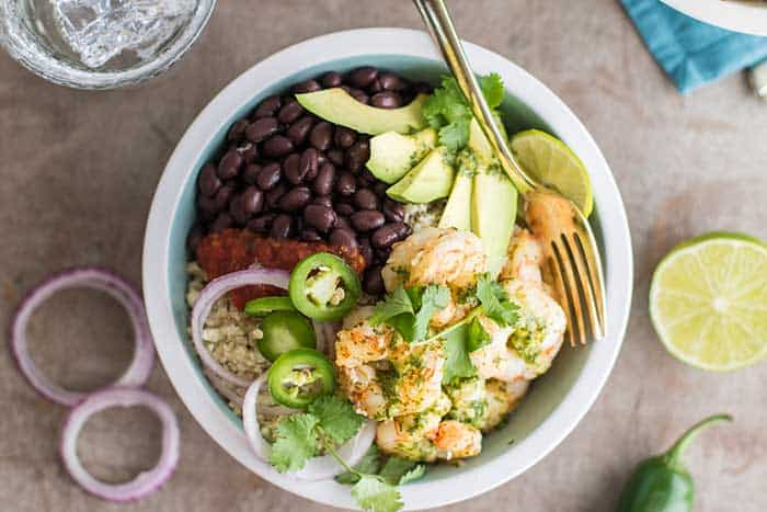 A top view of shrimp burrito bowls loaded with cauliflower rice, black beans, avocado, salsa and onions.