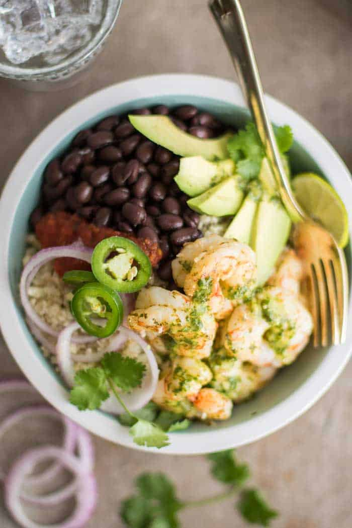 A loaded low carb burrito bowl, topped with cilantro lime marinated shrimp.