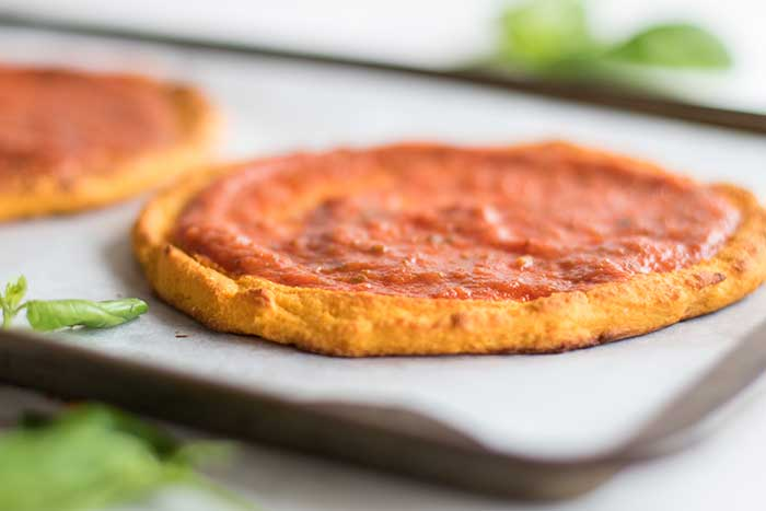 A paleo sweet potato pizza crust spread with pizza sauce.
