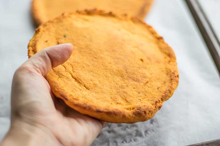 Holding a sweet potato pizza crust baked in hand to show how sturdy they are.