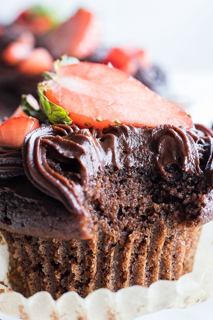 A closeup of a paleo chocolate cupcake with a bite taken out of it.