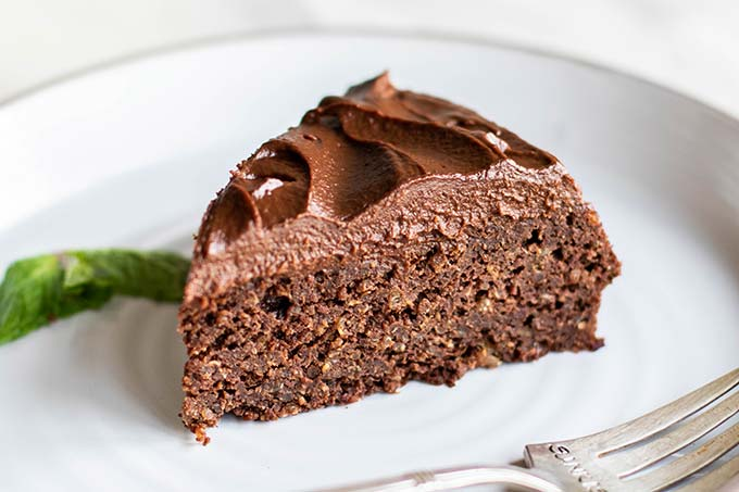 A piece of chocolate cake with a thick layer of healthy chocolate frosting.