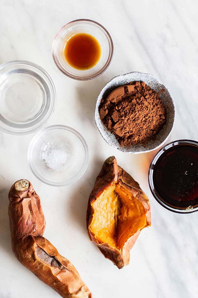 The ingredients for healthy chocolate frosting prepared and ready, including baked sweet potatoes, cocout oil, cocoa powder, date syrup, and vanilla.