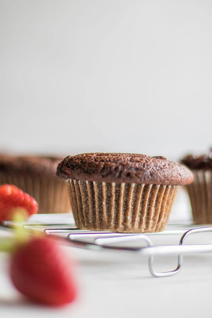 A chocolate cupcake surrounded by strawberries.