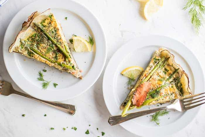 Two plates each with a slice of whole30 frittata with smoked salmon and asparagus.