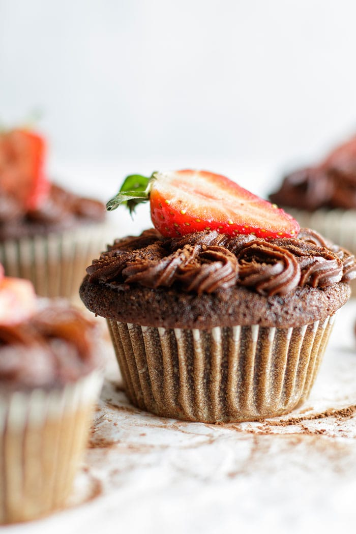 A healthy chocolate cupcake with a strawberry.