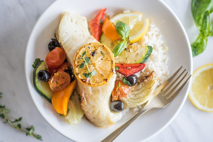 A piece of baked cod topped with a lemon slice, on a plate with rice and mediterranean vegetables.