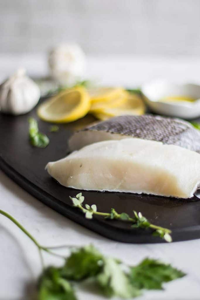 Two cod fillets on a cutting board with lemon and garlic.