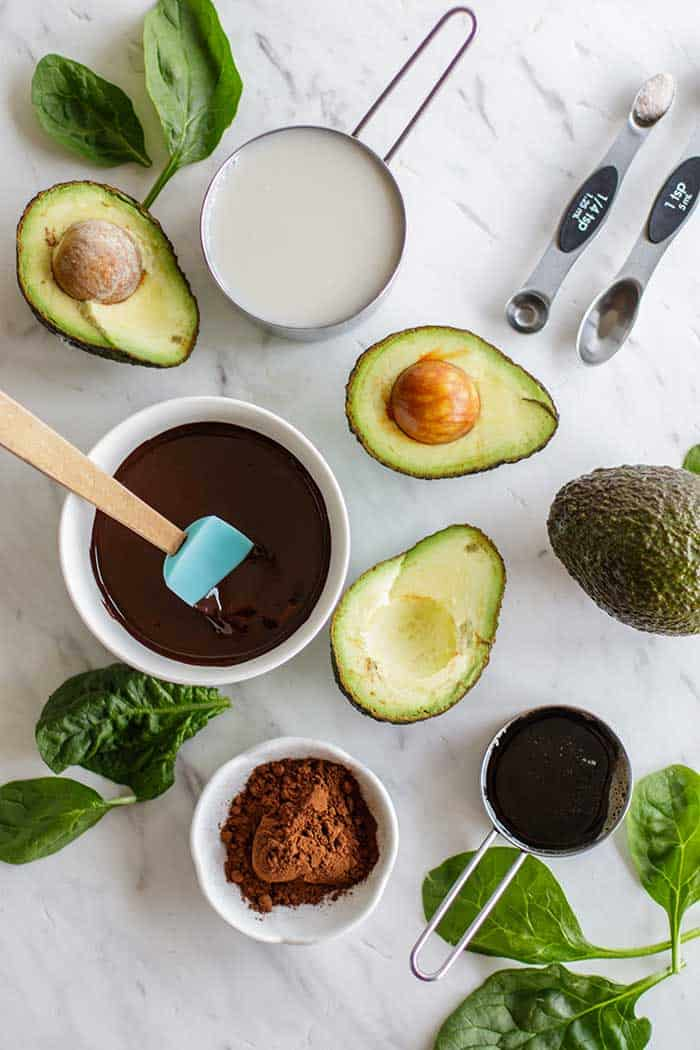 The ingredients in chocolate avocado pudding, including avocado, melted chocolate and cocoa powder.