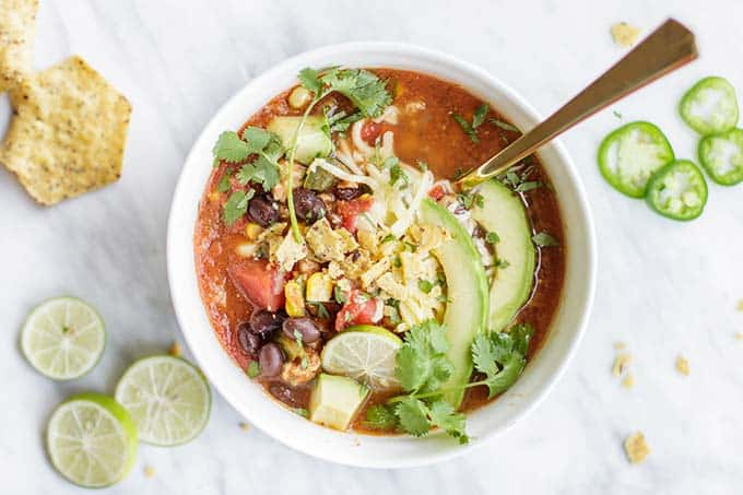 A bowl of soup filled with lots of toppings.