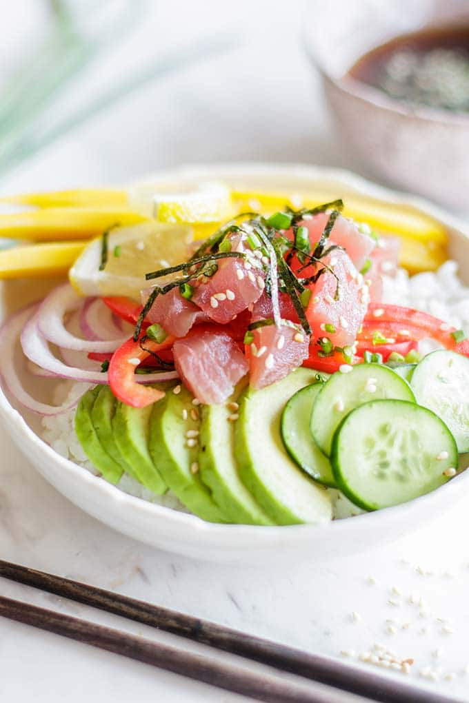 A side view of a rice bowl topped with ahi tuna, avocado, mango, onions and cucumber.