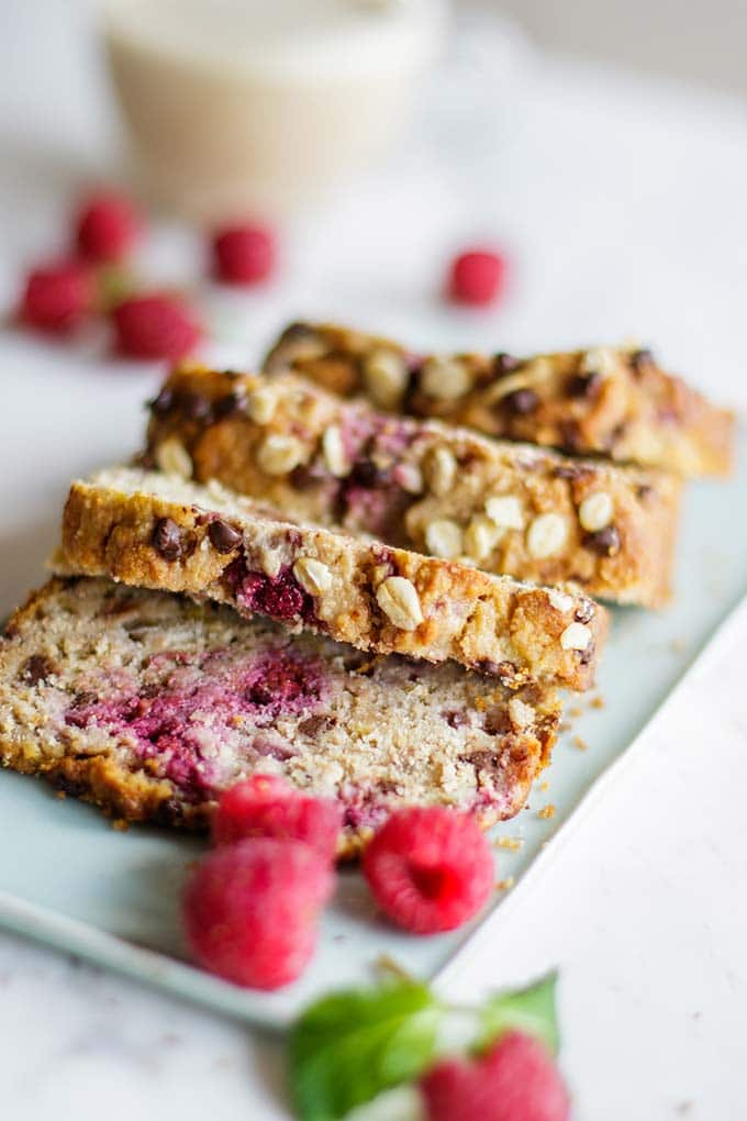 Thick cut slices of gluten free banana and raspberry bread on a blue plate.