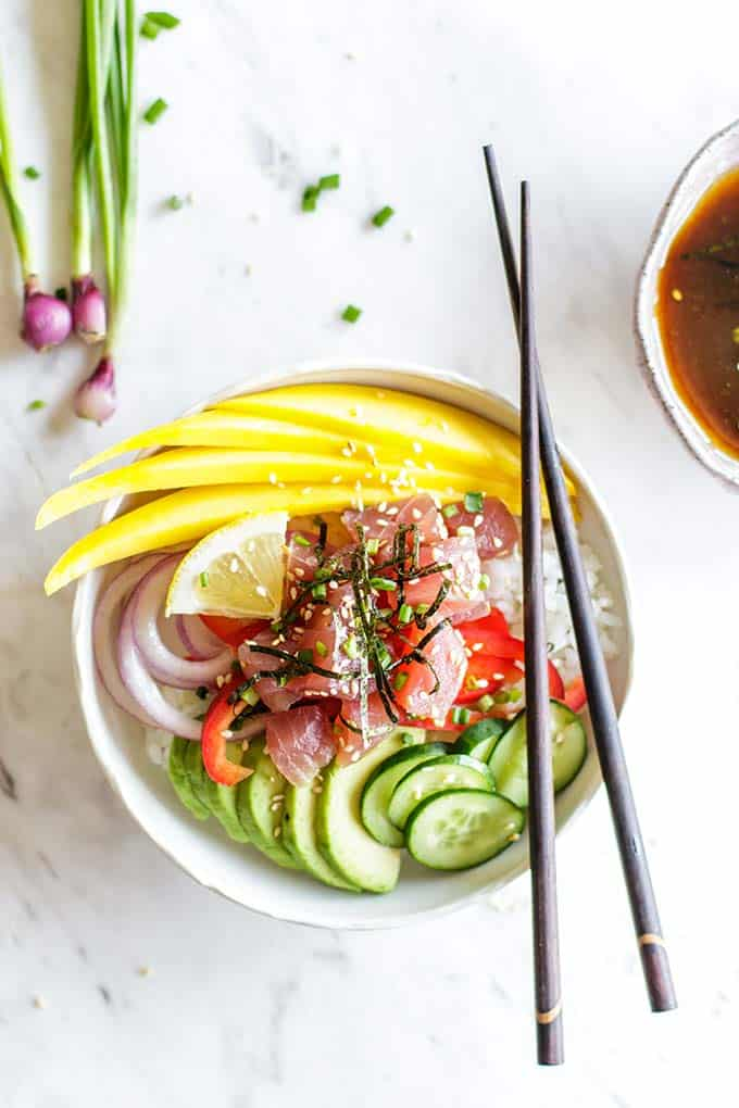 A poke bowl with ahi tuna, avocado, onion, mango and cucumbers.