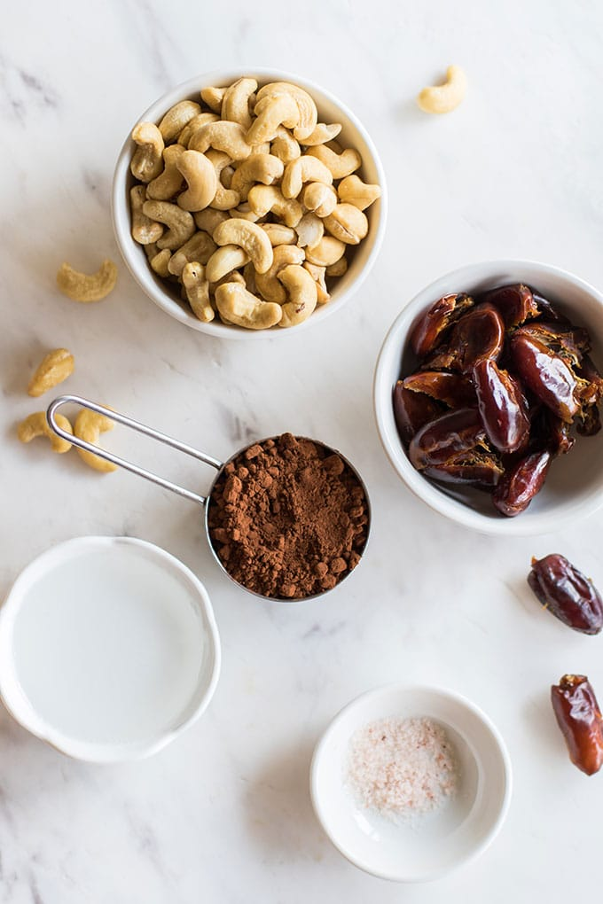 The ingredients for raw vegan brownies shown in bowls and measuring cups.