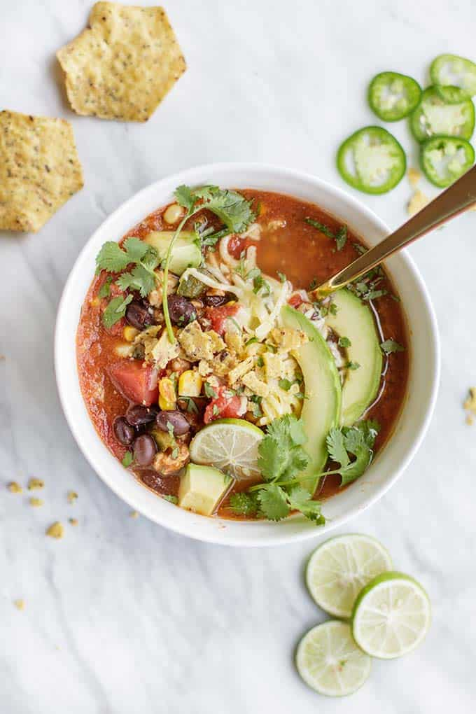 An overhead shot of a bowl of taco soup with avocado, cilantro and salsa on top.