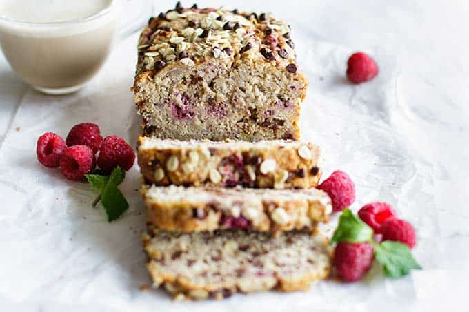 A loaf of healthy banana raspberry bread cut into thick slices.