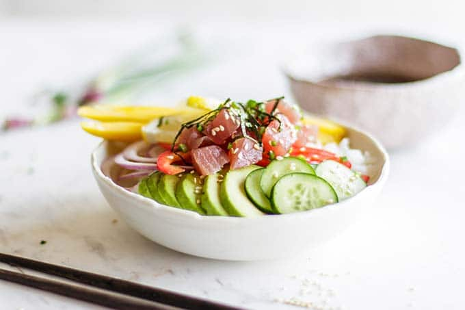 A poke sushi bowl loaded with toppings, with a bowl of sauce on the side.