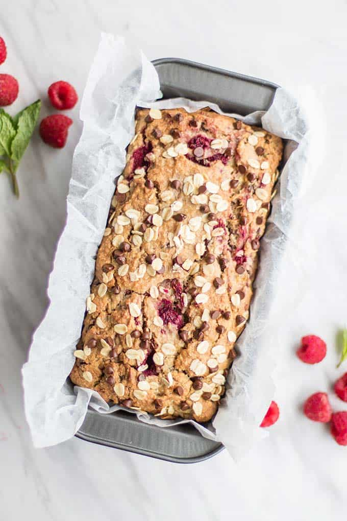 A baked loaf of banana raspberry bread still in the pan.