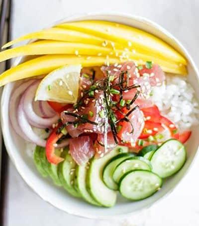 A hawaiian poke bowl recipe with ahi tuna, garnished with avocado and mango.