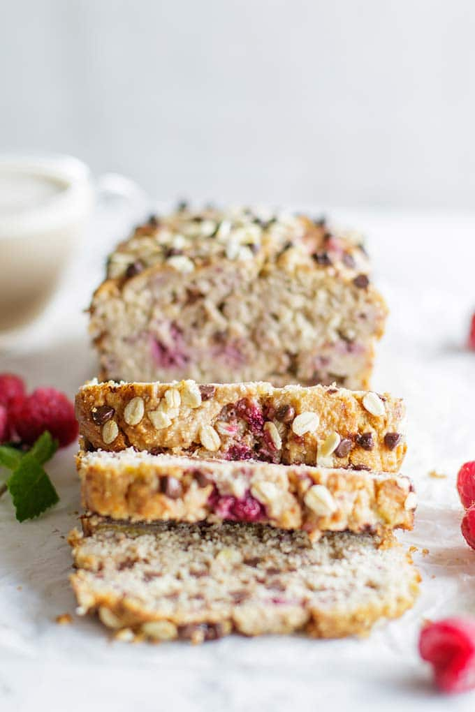 A loaf of banana raspberry bread cut into thick slices and stuffed with dark chocolate chips.