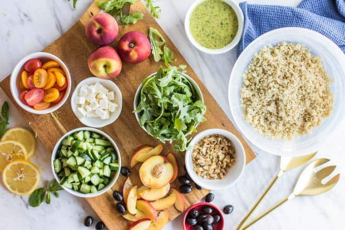 A cutting board covered in ingredients for a greek quinoa salad.