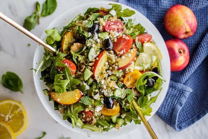 A quinoa salad with feta, nectarines, olives, tomatoes and arugula.