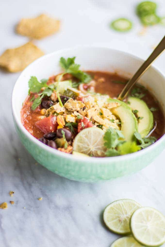 A bowl of this taco soup recipe with limes, chips, and jalapeno slices.