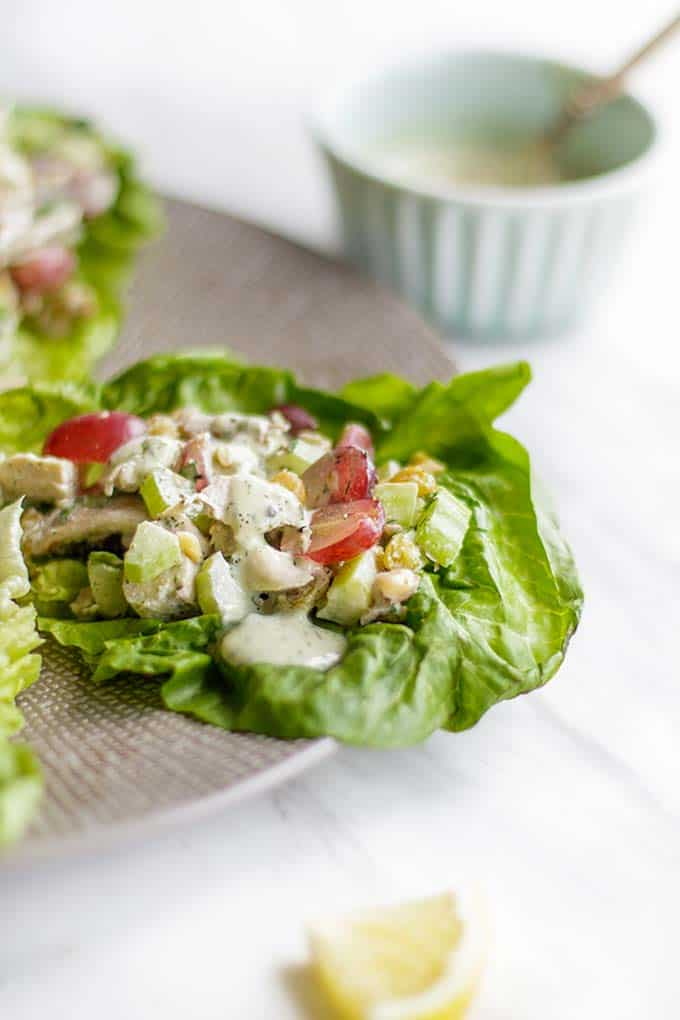 A plate with 4 leaves of lettuce packed with Whole30 Chicken Salad.