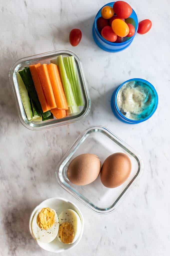Healthy travel snacks, including hard boiled eggs, veggie sticks, and dip.