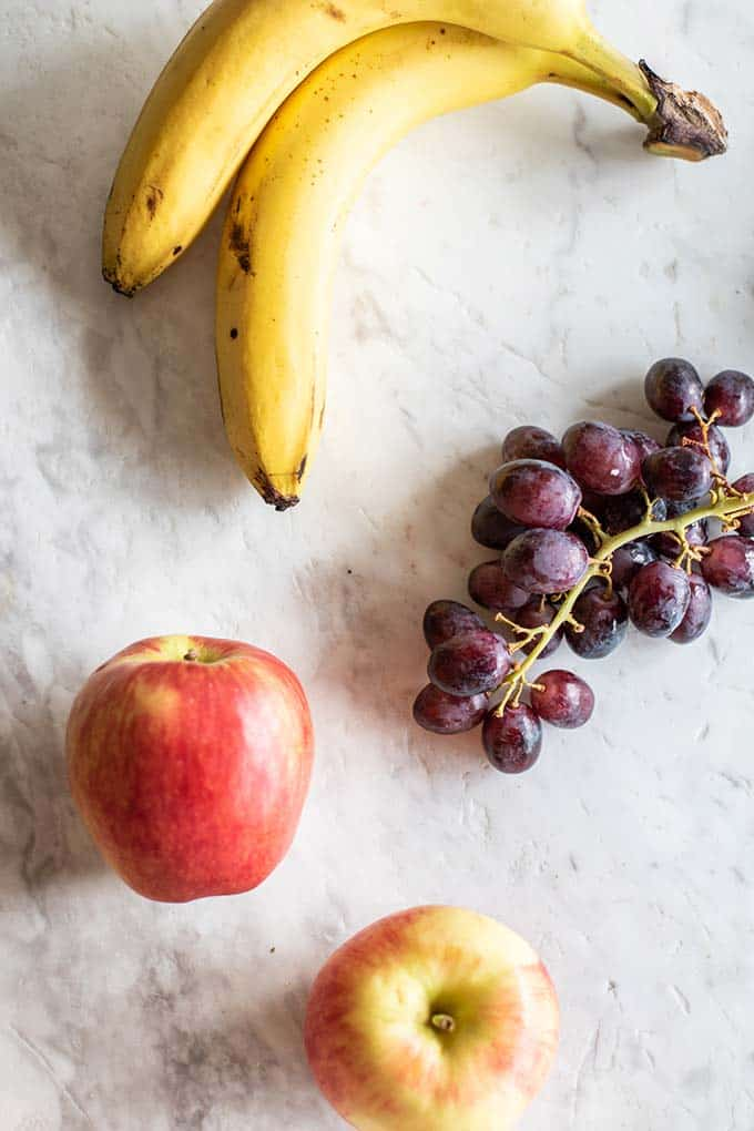 Fruit that makes good travel snacks, showing apples, bananas, and grapes.