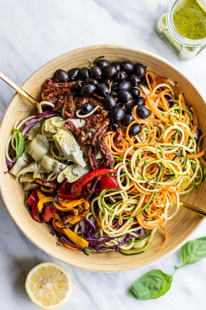 A large salad bowl filled with spiralized zucchini and carrots, and topped with artichoke hearts, roasted peppers, olives, and sun dried tomatoes.