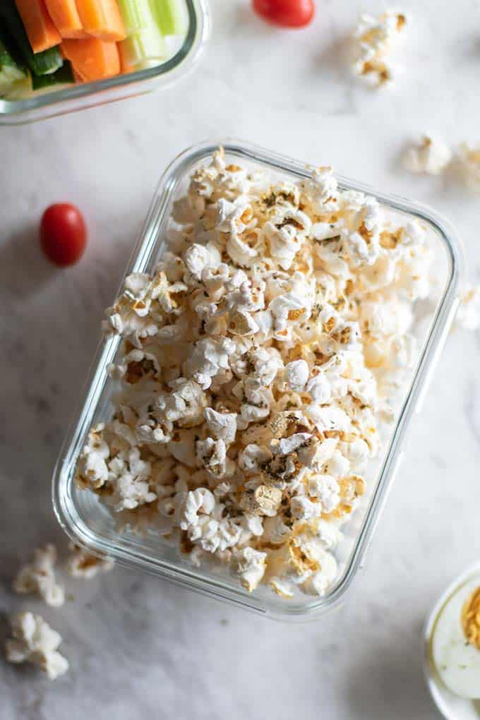 A glass container filled with popcorn, which is a suggested healthy plane snacks.
