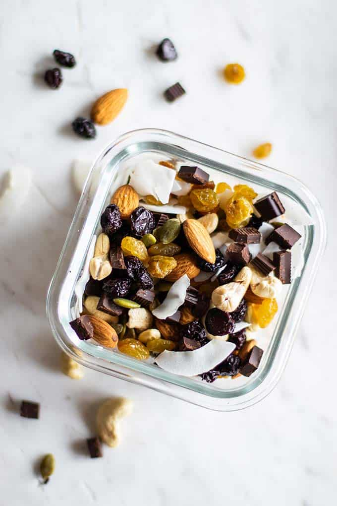A close up of a container packed with trail mix, including nuts, coconut flakes, dark chocolate, and tart cherries.