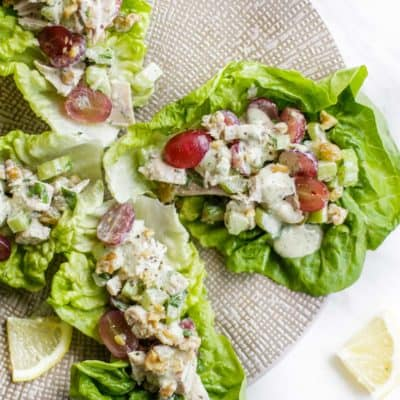 A plate with 4 leaves of lettuce filled with a paleo chicken salad.