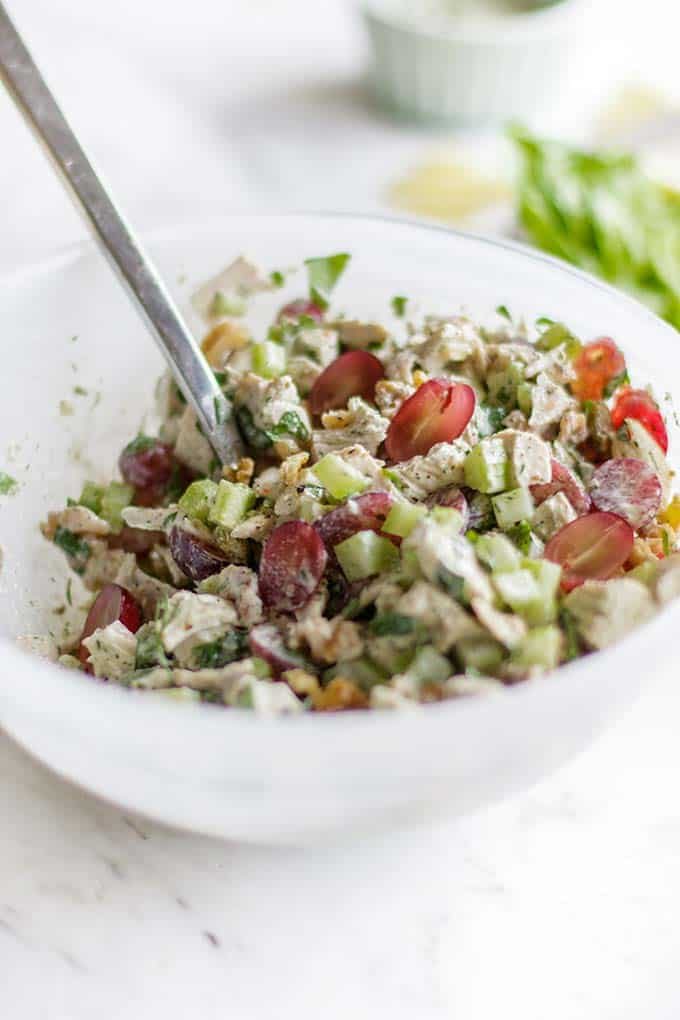 A bowl with Whole30 chicken salad, showing the additions of grapes, celery, walnuts and raisins.