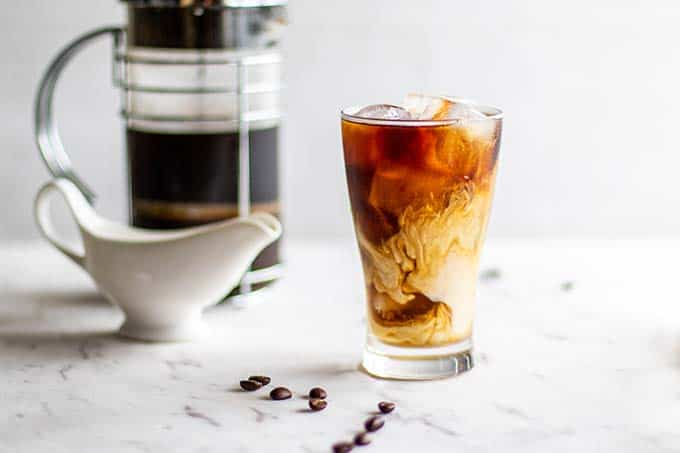An icy glass of cold brew coffee sitting in front of a French press.
