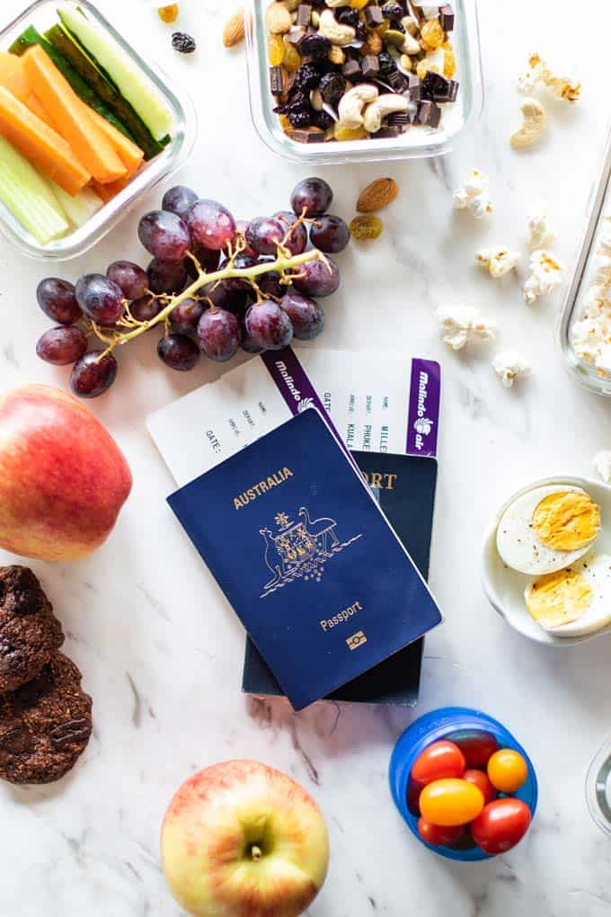 Two passports, surrounded by healthy airplane snacks suggestions.