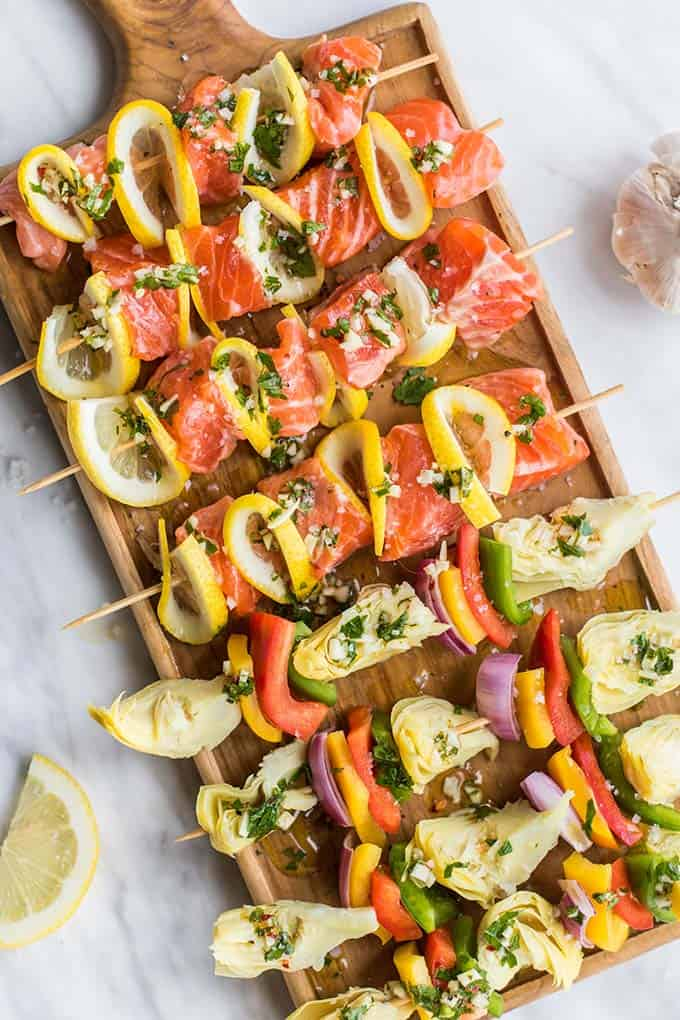 Salmon skewers prepared by alternating peppers, onions, and artichoke hearts on a wooden cutting board.