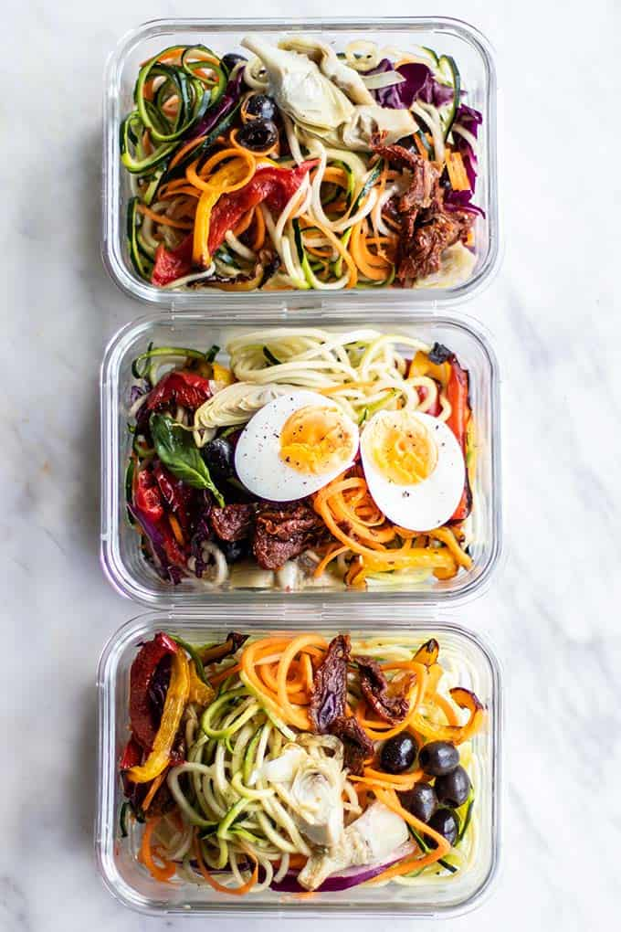 3 glass meal prep containers filled with a pesto zoodle salad, topped with a hard boiled egg.