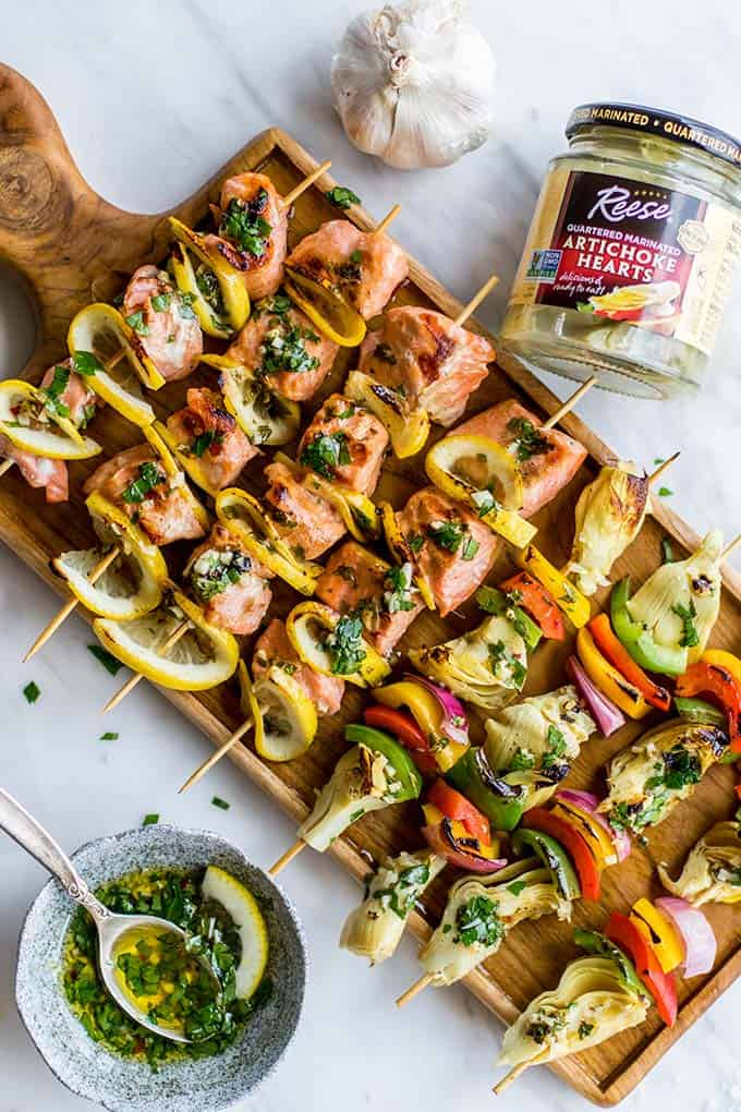 Grilled salmon skewers shown next to a jar of artichoke hearts.