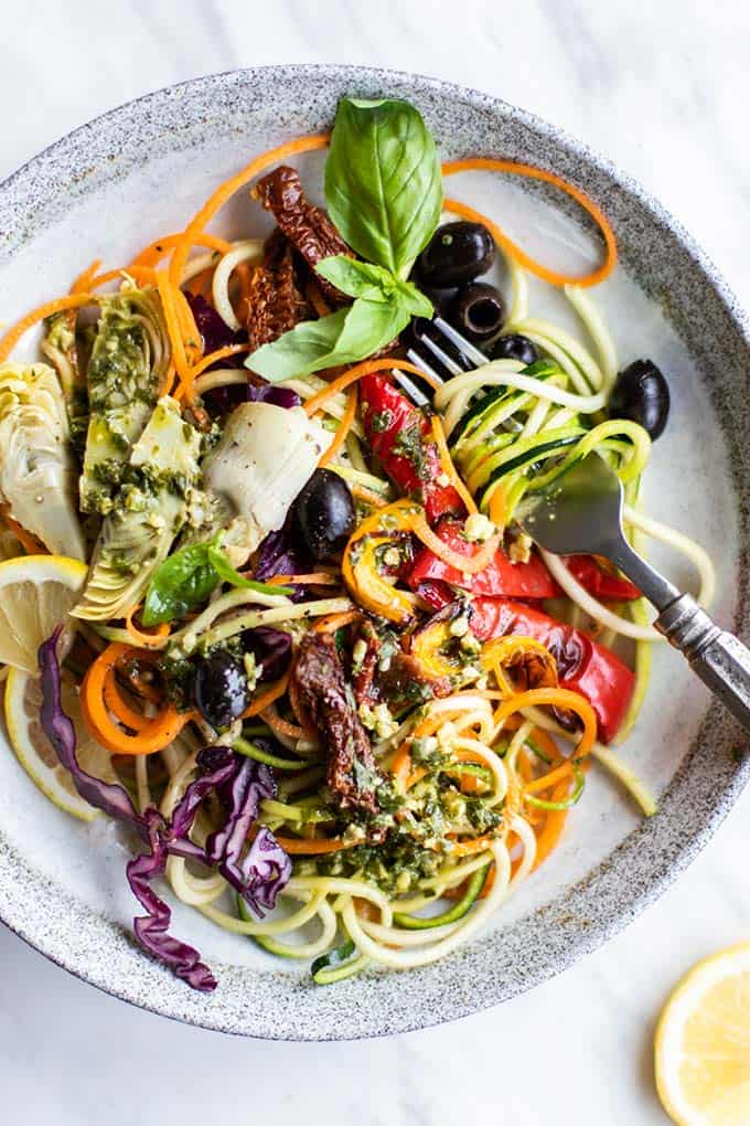 A close up shot of a pesto zoodle salad topped with artichoke hearts, peppers, sun dried tomatoes and olives.