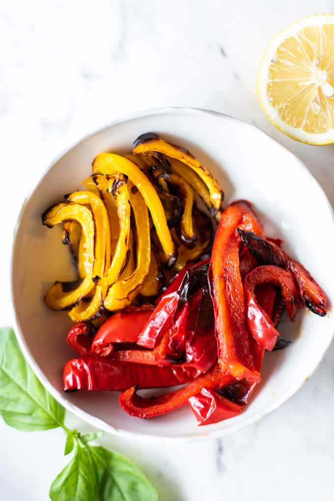 A bowl of red and yellow peppers roasted until slightly charred.