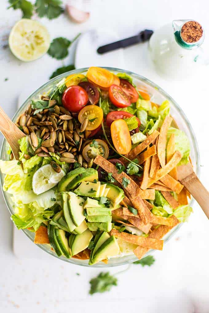 A bowl filled with romaine lettuce, tomatoes, avocados, toasted pepitas, and crunchy tortilla strips.