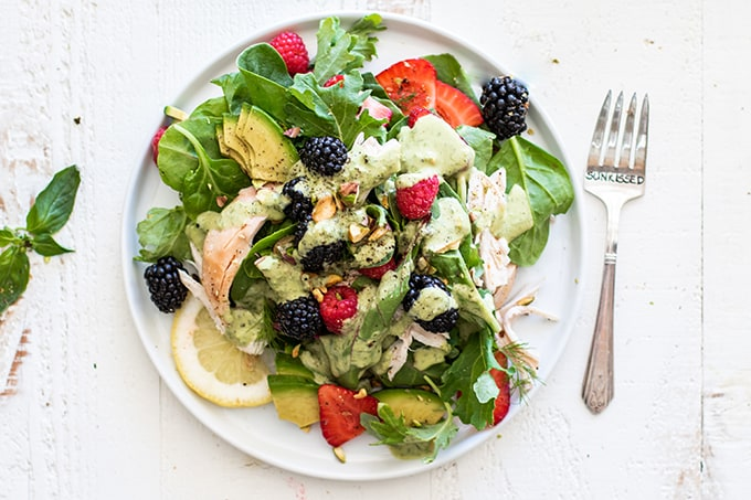 A plate with a chicken berry salad, with fork next to it.